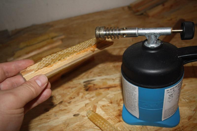 Mit einem Gasbrenner werden die kurzen Anfangsstreifen an den Holzleisten angeschmolzen, die Bienen bauen an diesen später die Waben aus